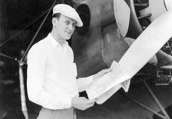 A publicity photograph of Clyde Allen Lee of Larsen, Wisconsin, standing beside the Stinson airplane he rebuilt to attempt a trans-Atlantic crossing to Oslo, Norway. Lee's airplane disappeared over the North Atlantic in 1932.