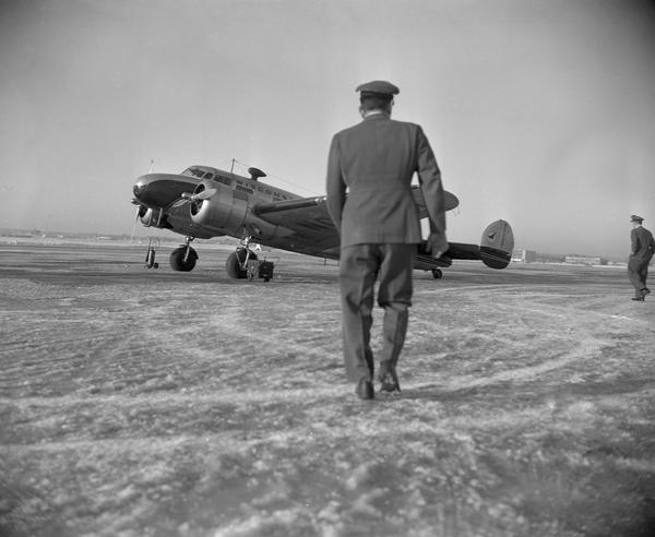 A Wisconsin Central Airlines pilot walking toward a twin-engine Lockheed 10A airplane parked on the runway at Truax Field.