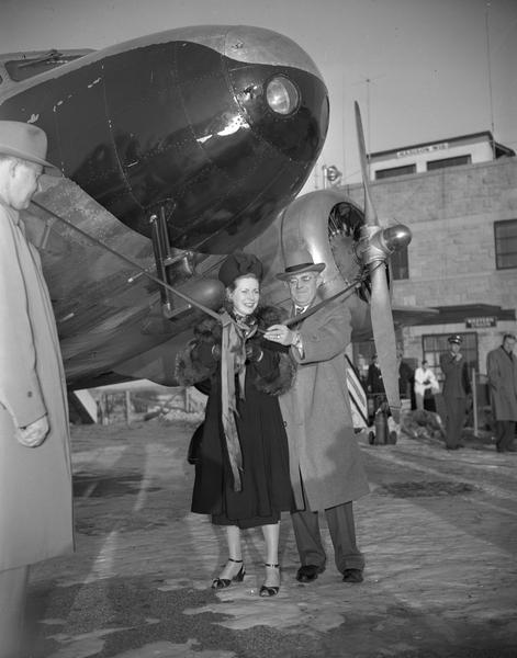 "The ceremony marking the first Wisconsin Central Airlines flight at Madison. Margaret ""Mickey"" Morey, the wife of Howard Morey, is about to cut the ribbon. She is standing beside J.C. Higgins, president of the airlines. Wisconsin Central originated in Clintonville in 1944, but moved its headquarters to Madison in 1948 when the Air Force gave up its lease at Truax Field. Howard Morey became president of the airline after it moved to Minneapolis in 1952."