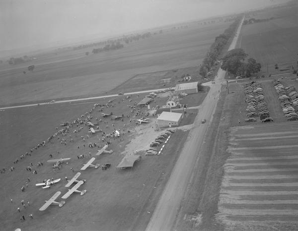 An aerial view of the air show at Tri-County Airport to celebrate the re-opening of the field under local management. Because of its location at the intersection of two mail routes, a tiny airport was established at Lone Rock.  In 1954, the Civil Aeronautics Administration relinquished control and operations were taken over by Sauk, Richland, and Iowa counties.