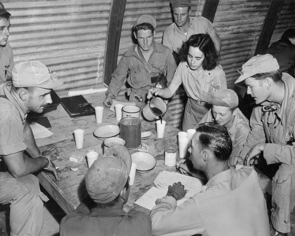 Betty Sullivan, a Red Cross worker, serves coffee in the interrogation room at Kobler Field, Saipan, for a B-29 flight crew that had just returned from a bombing mission.  This photograph is one of a large of number of studies taken by Milwaukee photographer Dickey Chapelle during the latter stages of the war in the Pacific.