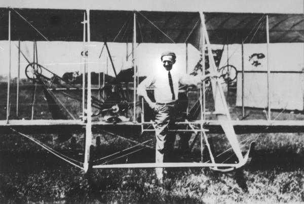 "Chicago Tribune cartoonist John T. McCutcheon with his Wright Model B airplane, probably photographed at Cicero Field. McCutcheon is sometimes referred to as the ""Dean of American Cartoonists."" Jesse Brabazon, owner of the album from which this photograph comes, recalled McCutcheon as a ""proficient pilot"" and an active member of the Chicago Aero Club."