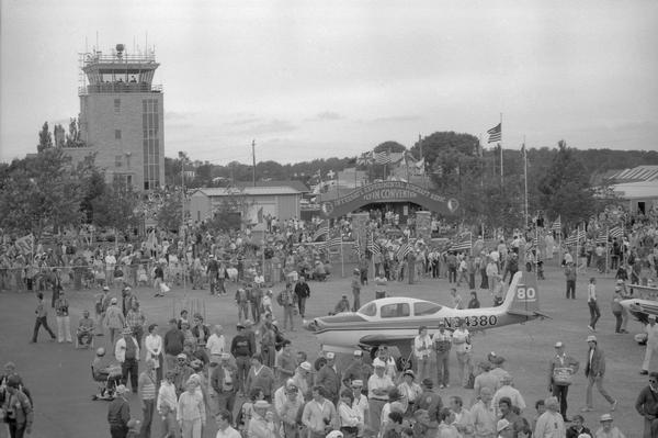 Elevated view of Experimental Aviation Association (EAA) crowds at Wittman Field in Oshkosh during the mid 1980s. The control tower is in the background.