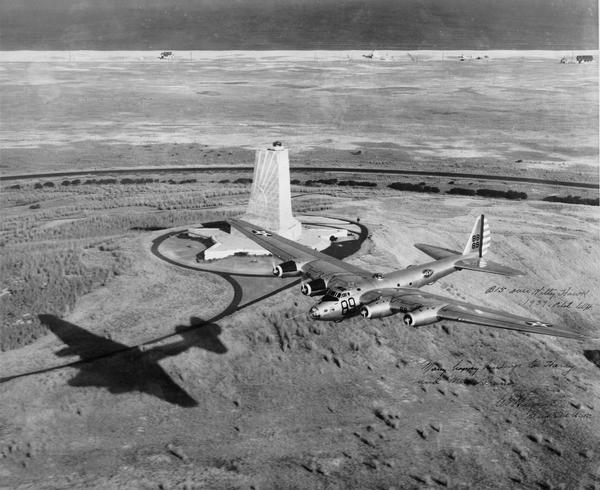 Aerial view of a B-15 flying over the granite memorial to the Wright Brothers' first flight at Kitty Hawk, North Carolina. The 60-foot memorial was dedicated in 1932. This photograph is inscribed to aviation publicist Harry Bruno from the pilot, Major General Caleb V. Haynes, the winner of the 1939 Mackey Trophy for achievement in aviation. At its introduction in 1937 the B-15 was the largest U.S. Army bomber, but because it was underpowered, only one B-15 was ever built.