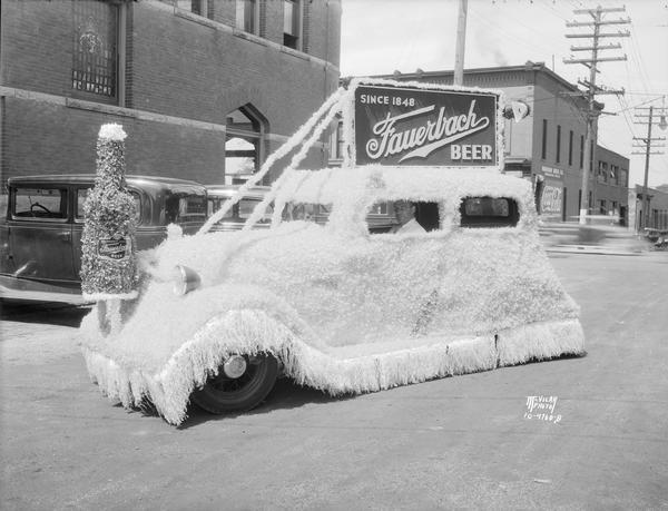 An automobile covered in crepe paper with a beer bottle on the front end, and a sign on the top serves as the Fauerbach Brewing Co. float. It was built to be in a parade celebrating the opening of Park and Regent Streets. Taken in front of the Fauerbach building, the Madison Drug Company at 654 Williamson Street.