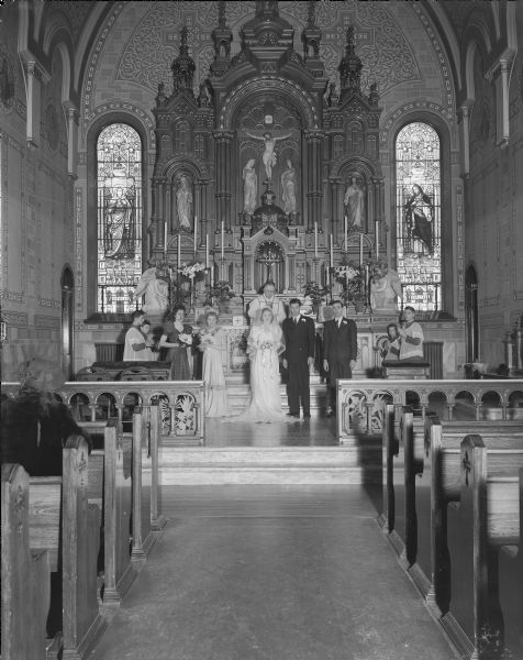 Wedding party at the altar of Sacred Hearts Catholic Church. Party includes bride Marian Thekla Hebl, groom James Daniel Tormey, Priest George Haeusler, bridesmaids Arlene Hebl and Iona Miller, best man John Tormey and four altar boys.