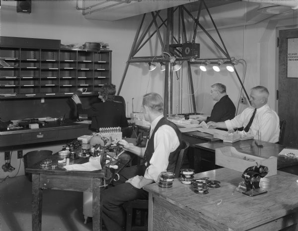 Three men are making microfilm copies of birth records in the microfilm department at the Wisconsin State Office Building (Capitol Annex), 1 West Wilson Street.