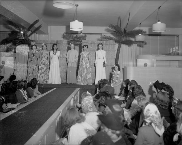 Women's style show (for McCall's) at Manchesters Department Store with six female models wearing long dresses on stage, and a female announcer at the microphone.