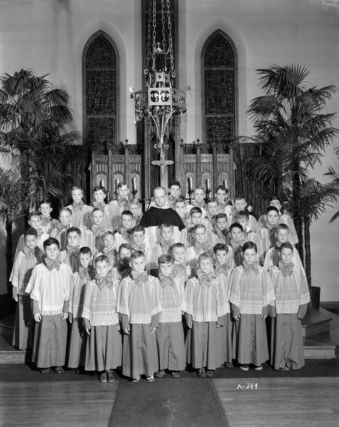 Blessed Sacrament Catholic Church boys' choir grouped in front of the altar, with The Reverend James A. McInerney (Father Mac) in their midst. The church is located at 2119 Rowley Avenue.