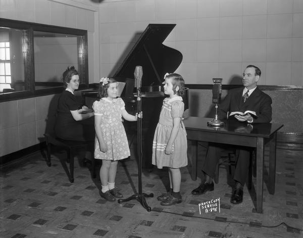 Reverend C.O. and Mrs. Grobber and two daughters at WIBU radio station studio. Reverend Grobber is sitting in front of a microphone, Mrs. Grobber is at the piano, and the daughters are standing at another microphone.