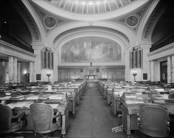 "Interior view of the Assembly Chamber at the Wisconsin State Capitol, with seating for legislators, featuring the Edward Blashfield mural, ""The State of Wisconsin, its Past, Present, and Future""."