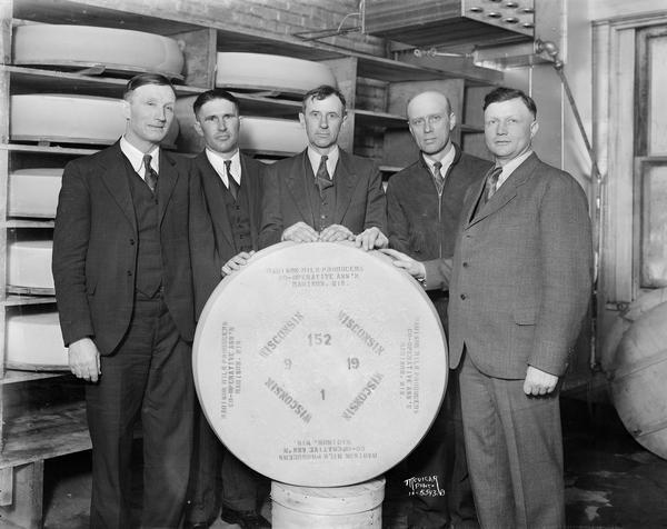 "Five men stand behind a 200 pound wheel of Swiss cheese. Written on wheel is ""Madison Milk Producers Cooperative Ass'n."" The cheese was a gift for Major Edward Bowes for featuring Madison on his radio amateur talent show. 29 Coyne Ct."