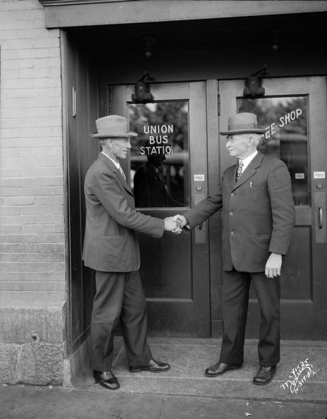 George A. Nelson, Milltown, former assemblyman and president of the Wisconsin Union of the American Society of Equity, and John E. Cashman, Denmark, State Senator, shaking hands in front of the Union Bus Station.