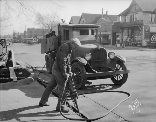 Man with jackhammer making street repairs with an air hammer with compressor. Wisconsin Foundry & Machine Co. Saunders Grocery store is across the street at 733 University Avenue.