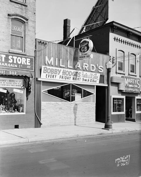 "Millard's Tavern, 504 East Wilson Street with Fauerbach CB beer sign and ""Bobby Hodges radio & TV star, Every Friday Night."" Also shows Marty's Sandwich Shop, 506 East Wilson Street and Factory Outlet Store, 502 East Wilson Street."