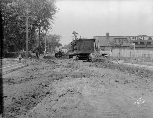 "Steam shovel loading a truck as part of road construction in front of Collins Lumber Co., 2308 University Avenue. There is a horse-drawn wagon passing by. Text on back of print reads: ""Univ. Ave. Construction at Walnut St. — looking W. Steam Shovel loading truck. Collins Lumber Co. -2308."""