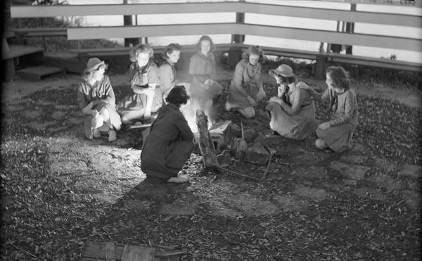Eight Girl Scouts kneeling around a campfire inside a campfire ring at Camp Indianola.