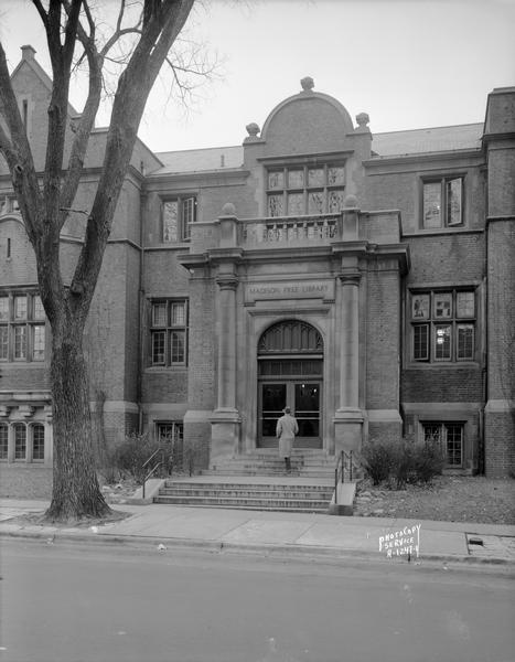 View from street towards a man approaching the entrance to the Madison Free Library, 206 North Carroll Street. The library was built with Carnegie money and opened in 1906. The name changed to Madison Public Library in January 1959.   This building was torn down in 1965 when the library moved to a new building at 201 West Mifflin Street.