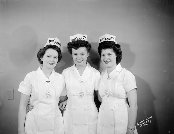 "Three female employees of Rennebohm Drugstore #2, 204 State Street, wearing white  uniforms, caps and neckties with slogans urging people to buy war bonds: ""Third Party, Private, Fifth War Loan, Retailers for Victory."""