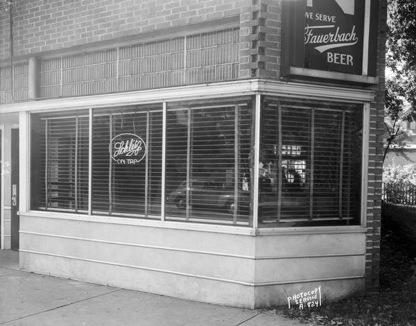 "Arian's Tavern, 2517 University Avenue. The windows have Venetian blinds, and a Schlitz beer neon sign. At the corner of the building on the right is a ""We Serve Fauerbach Beer"" sign."