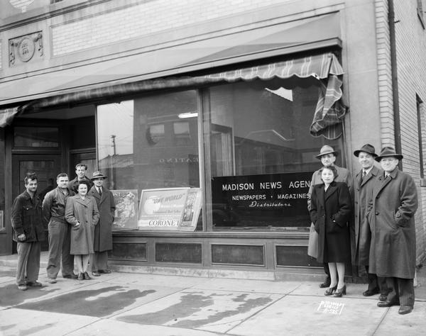Group portrait of employees of the Madison News Agency, distributors of magazines and newspapers, in front of the business at 446 W. Gilman Street.