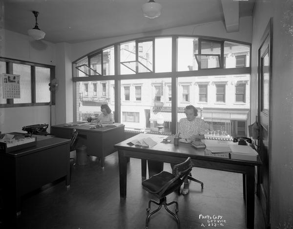 Office interior on the second floor of the Capital City Bank Building, 111 King Street, also known as the King Street Arcade, with two female office workers at desks.