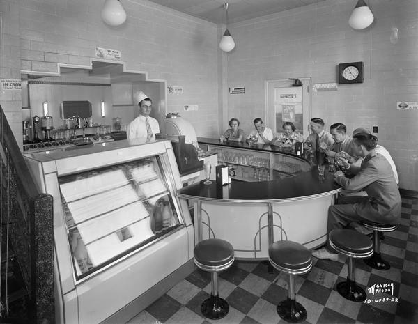 A male soda jerk is standing behind the semi-circular counter in the Bancroft Dairy fountain room, with seven customers eating ice cream.