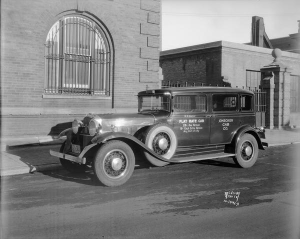 Checker Cab Company flatrate cab in front of the Chicago & Northwestern railroad depot at 148 S.Blair Street.