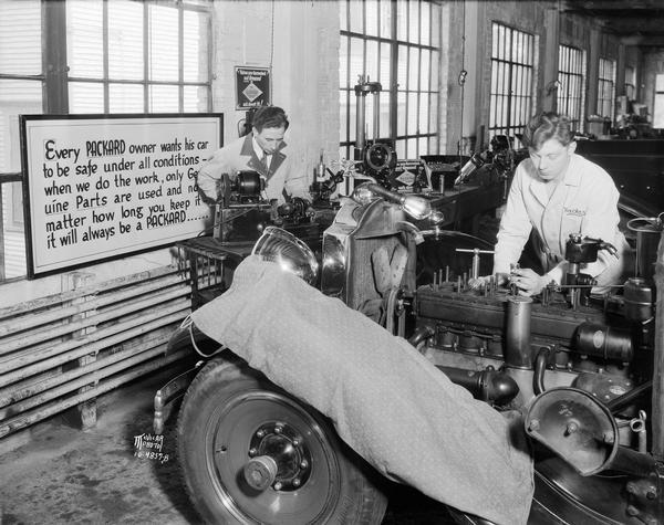 At Gabbei Motor Co. at 412 East Washington Avenue, one man works on the engine of a car while another machines a part in the company garage.