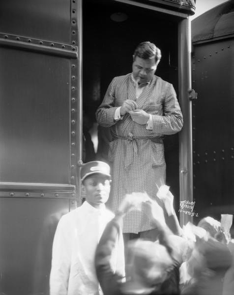Babe Ruth, wearing dressing gown, stands in the doorway of a train and signs autographs for clamoring fans, with a train porter in uniform standing by.