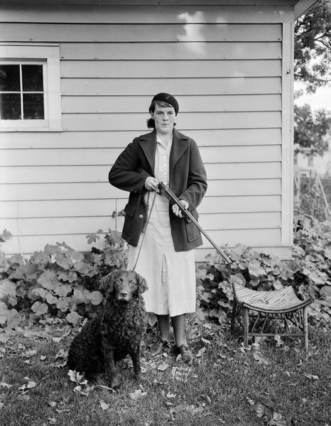 Ruth L. Brissee holding a rifle, standing with her dog in a garden at 2437 Fox Avenue. At age 15 she is the youngest huntress in Dane County.