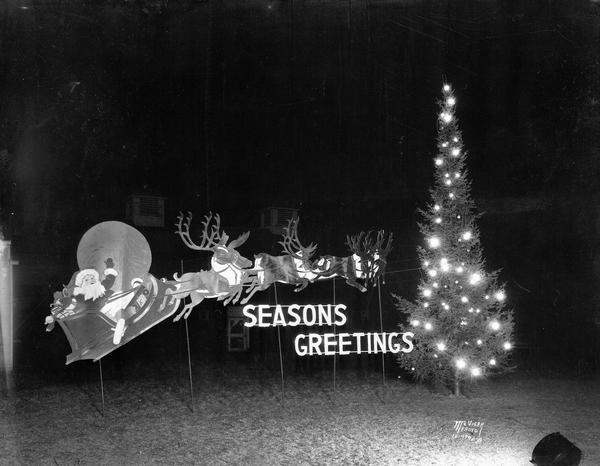 Night view of outdoor Christmas display (Santa Claus, reindeer, and Christmas tree with lights) in front of Conklin and Sons, 322 East Gorham Street at North Hamilton Street.