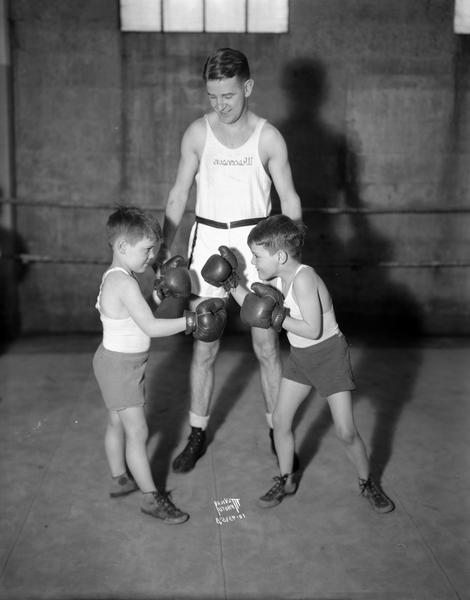 Young boys, Alex and Bobby McCormick, posing as boxers in front of John Walsh, University of Wisconsin boxing coach.