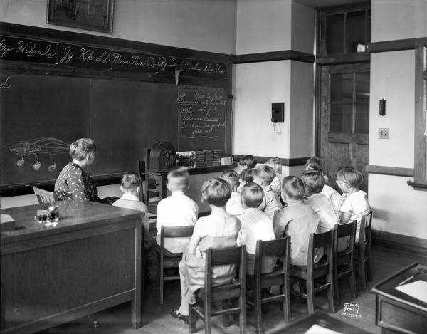 Emerson School children and teacher listen to a radio broadcast from a radio set up in front of the blackboard in the classroom at 2421 East Johnson Street.