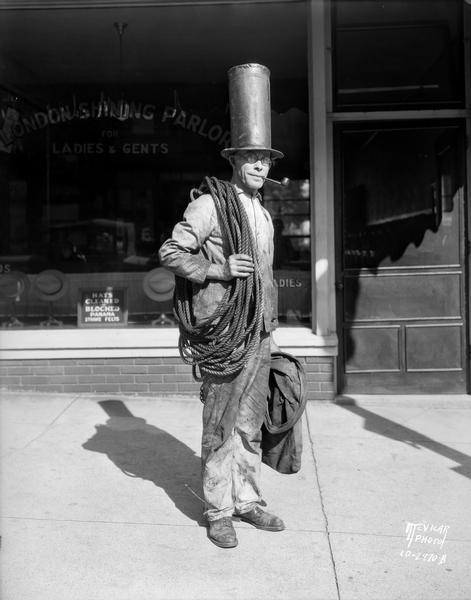 Portrait of George Stahl, chimney sweep, with a pipe in his mouth, and wearing a tall hat and carrying a bag and a rope around his shoulder. He is standing in front of the London Hat Cleaners, 230 King Street.