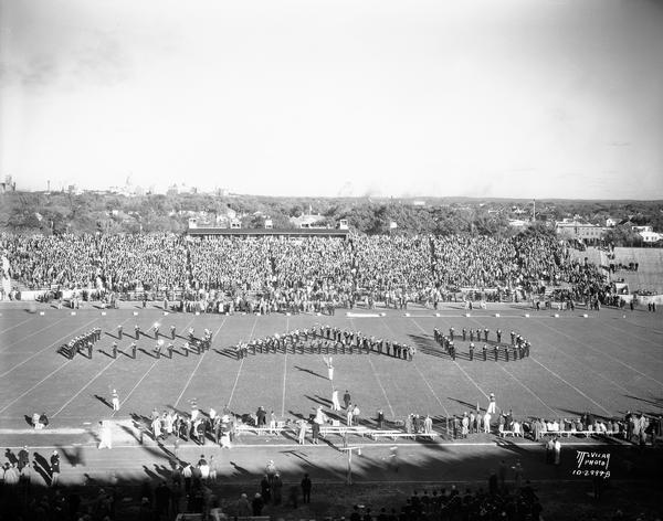 "University of Wisconsin band marches in a ""DAD"" formation at the Wisconsin-Purdue football game. The dome of the Wisconsin State Capitol is in the background."