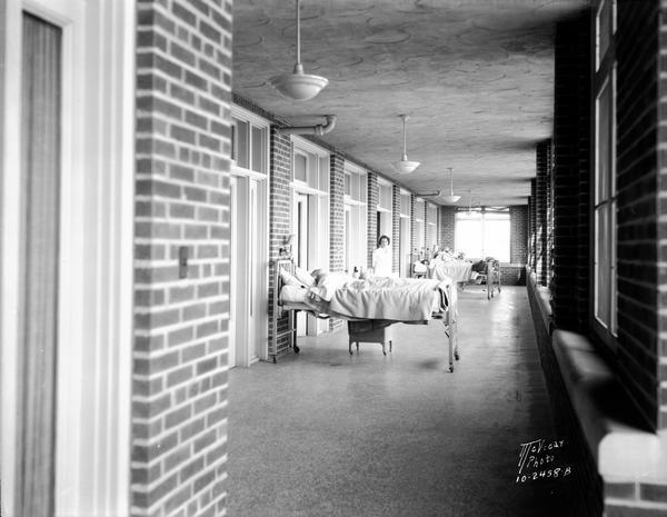 View towards patients in beds, with nurses, on the sun porch at the Lake View Tuberculosis Sanitarium.