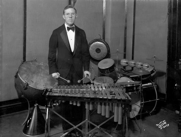 A tuxedo-clad percussionist stands at his marimbas, with other instruments including a gong, drum kit, and tympani behind him at the WIBA radio station.