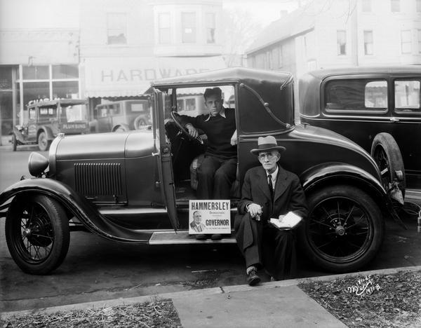 Mr. Cranefield and another man posing with a campaign sign in support of Hammersley for Governor of Wisconsin. One man is sitting in the driver's seat, and the other man is sitting on the running board of the automobile.