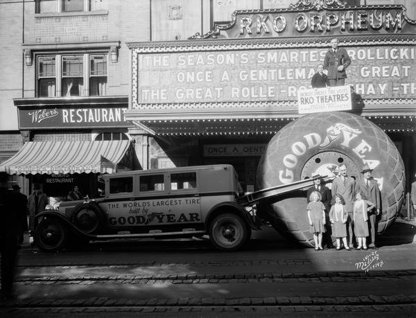 "Group of people, including dwarfs and midgets, posing with ""the worlds largest tire"" in front of the RKO Orpheum Theatre as part of a promotion for Goodyear Tires. ""Once a Gentleman"" is on the marquee."