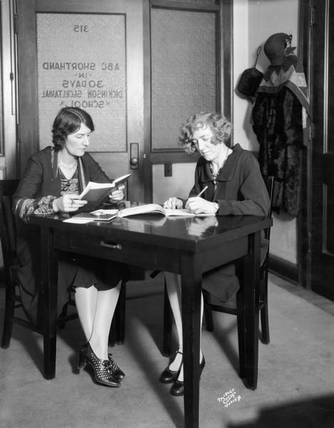 A women dictates to another student practicing for ABC shorthand at the Dickinson Secretarial School, 105 Monona Avenue.
