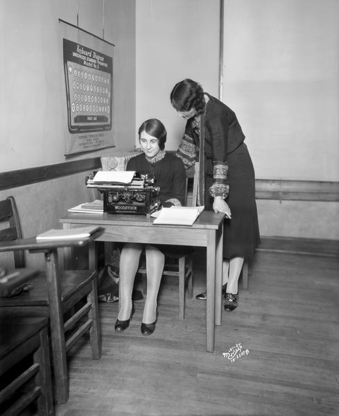 Mrs. Florence J. Blumer, standing, giving individual instruction in typewriting on a Woodstock typewriter to Miss Letha Luchsinger, of Belleville, a student at the Dickinson Secretarial School, 105 Monona Avenue.