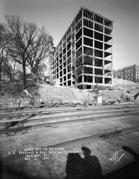 View of the State Office Building, 1 W. Wilson Street, under construction, from Lake Monona. The photographer's shadow and railroad tracks are in the foreground.