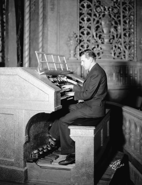 An organist is playing the Eastwood Theatre organ, located at 2090 Atwood Avenue. The organ grill is in the background on the far wall.