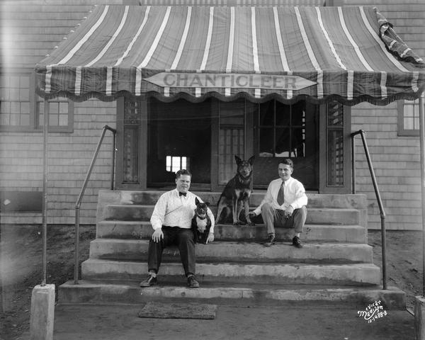 "Chanticleer Orchestra managers, each with a dog at his side, sit on the front steps of a building with an awning overhead that reads ""Chanticleer."""