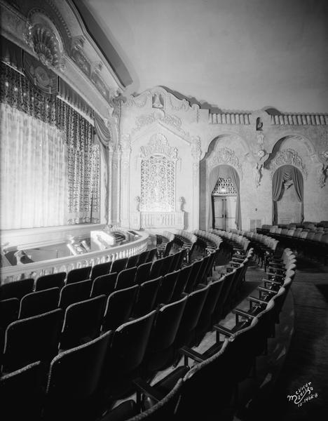View of the Eastwood Theater proscenium arch, grills, orchestra pit, and front few rows of seating, with decorative detail along the side of the auditorium.