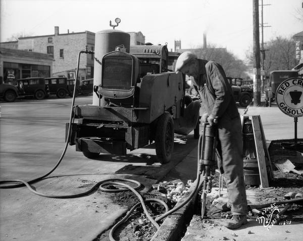 A worker is using an air hammer with compressor truck to do work on the road in the 800 block of University Avenue, looking west. Wisconsin Foundry & Machine Co.