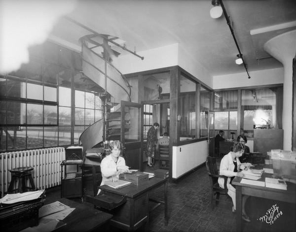 Office staff at work in Mautz Paint & Glass Company office, 939 East Washington Avenue. There is a spiral staircase on the left leading up to the next floor. Breese Stevens athletic field can be seen through the windows in the background.
