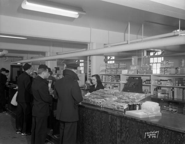 Female clerk selling items to Naval trainees at the U.S. Naval Training School (Radio) ship's store. The store was located in a University of Wisconsin dormitory.