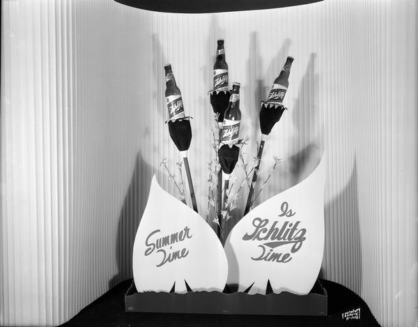 "Schlitz display with four bottles of beer displayed as flowers with sign ""Summer Time is Schlitz Time""."